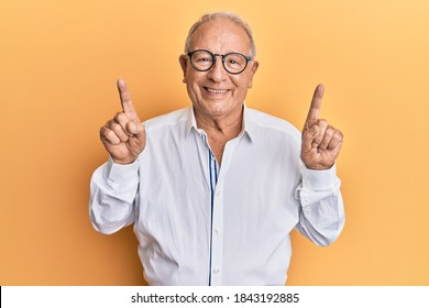 Senior caucasian man pointing up with fingers smiling with a happy and cool smile on face. showing teeth.