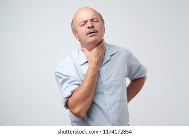 Senior caucasian man in shirt having pain in throat. Flu or other illness in cold winter. Studio shoot