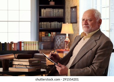 Senior caucasian man sitting in chair, wearing suit at home library, books on table, tablet computer in hand.