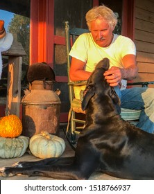 Senior Caucasian man sitting on his farmhouse porch with his faithful Great Dane dog on a beautiful sunny Autumn evening with equestrian gear saddle boots and pumpkins