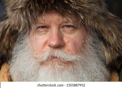 Senior caucasian man with splendid mustache and beard looking at camera against dark natural background. Extreme closeup face portrait of elderly stylish hipster wearing a fur cap with tabs over ears