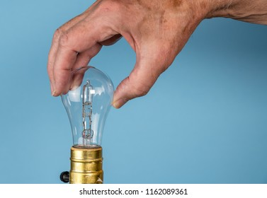 Senior caucasian man unscrewing a halogen lightbulb as concept for EU decision to ban the light bulbs