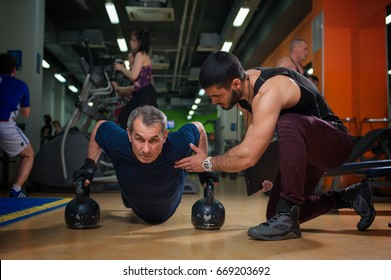 Senior caucasian man working out with personal trainer or fitness instructor in gym. Male adult doing push ups with kettle bells. Healthy lifestyle, fitness and sports concept.
