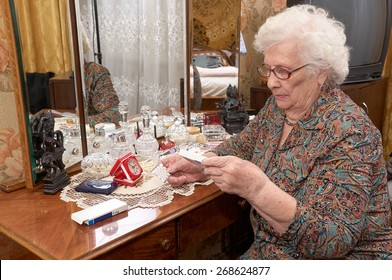 Senior caucasian woman about ninety years old sits near the mirror, takes out pills and reads prescriptions in her bed room