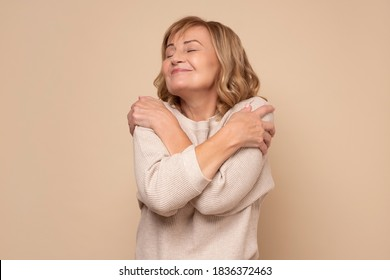 Senior caucasian woman hugging oneself happy and positive, smiling confident. Self love and self care concept.