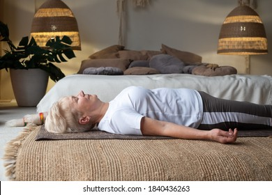 Senior caucasian woman lying on yoga mat after workout. Fit female relaxing on floor at home.