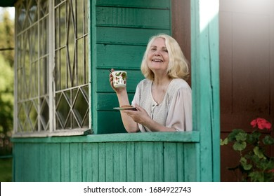 Senior caucasian woman portrait on sunny day standing near entrance of house and drinking cup of tea