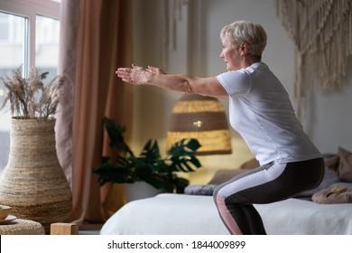 Senior caucasian woman practicing advanced yoga Chair Pose or Utkatasana at home