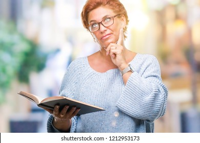 Senior caucasian woman reading a book over isolated background serious face thinking about question, very confused idea