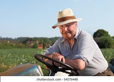 Senior, cheerful gardener on his tractor