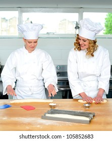 Senior chef teaching newbie female chef, how to roll and knead dough