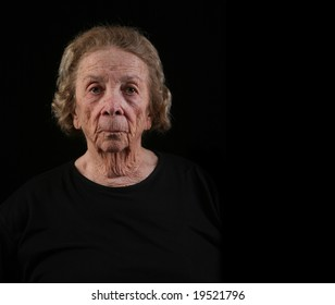 Senior Citizen Caucasian Woman in Deep Thought on Black Background