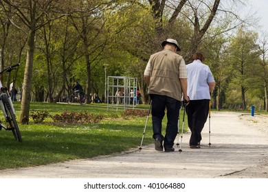 Senior citizen couple walking in the park with nordic walking poles.