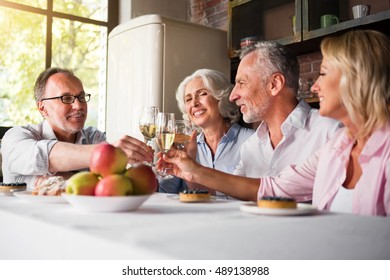 Senior citizen having birthday party cheering with wine