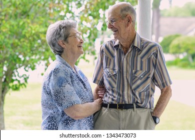 Senior citizens talking and smiling together while outdoors on a porch in Delcambre, Louisiana. Octogenarian couple happy and in love after 70 years of marriage. Two older happy adults now seniors.
