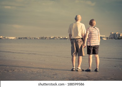 Senior citizens watching the sunset on a beach in Fort Myers, Florida. View from the back with copy space.