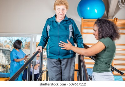 Senior citizens working out at a gym helped by multi race trainers.