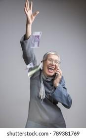Senior classy lady throwing money in the air, euro bills, enjoying wealth and prosperity