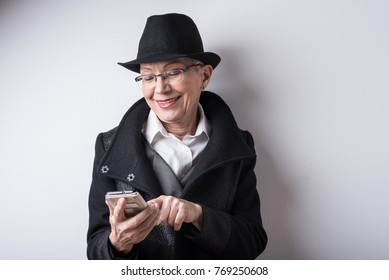 Senior classy old lady sending a text message over her cell phone