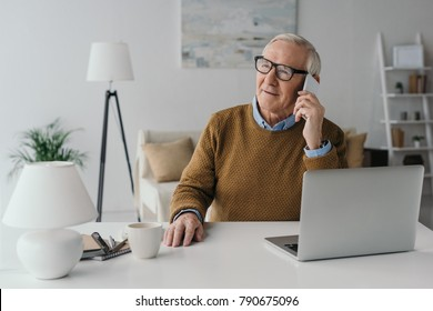 Senior confident man working in office and making phone call