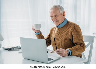 Senior confident man working on laptop and holding coffee cup