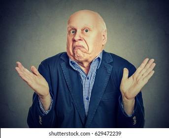 Senior confused man is shrugging his shoulders
