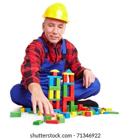 Senior construction worker playing with many colorful bricks