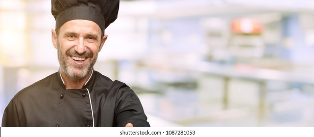 Senior cook man, wearing chef hat holds hands welcoming in handshake pose, expressing trust and success concept, greeting at restaurant kitchen