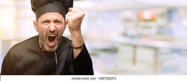Senior cook man, wearing chef hat irritated and angry expressing negative emotion, annoyed with someone at restaurant kitchen