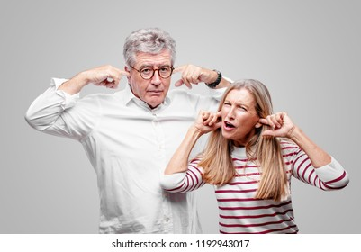 senior cool husband and wife with both hands covering ears to protect them from an uncomfortable, loud, annoying noise. Lateral or side view.