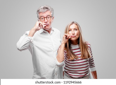 "senior cool husband and wife gesturing ""zip it"" with hand, demanding silence or secrecy with a serious, stern look."