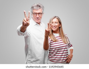 senior cool husband and wife smiling and looking satisfied and happy, counting number two with fingers.