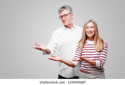 senior cool husband and wife smiling with a proud, satisfied and happy look, welcoming gesture or showing and recommending a concept, greeting you.