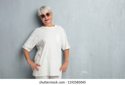 senior cool woman against grunge cement wall.