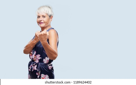 senior cool woman with an angry, aggressive and menacing pose, ready for the fight, showing fists furiously and belligerently.