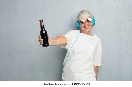 senior cool woman  having a beer against grunge cement wall.