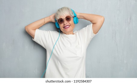 senior cool woman with headphones, listening music against grunge cement wall.