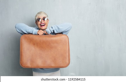 senior cool woman with a leather case against grunge cement wall.