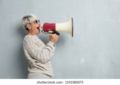 senior cool woman with a megaphone against grunge cement wall.