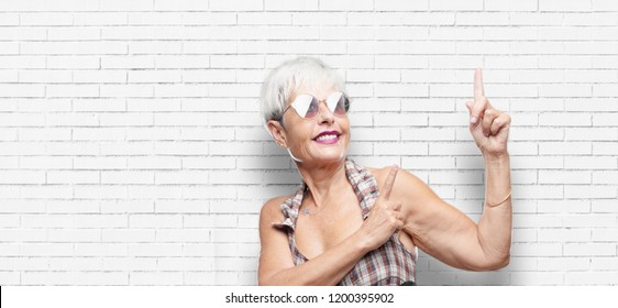 senior cool woman smiling and pointing upwards with both hands, towards the place where the publicist may show a concept.