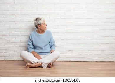 senior cool woman thinking against white brick wall background