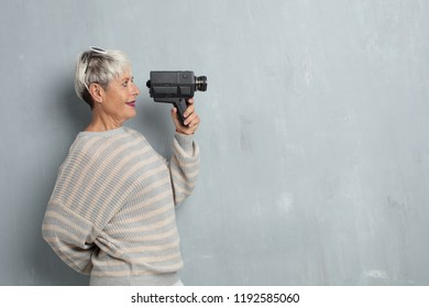 senior cool woman with a vinatge video camera against grunge cement wall.