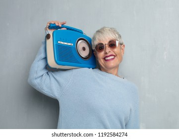 senior cool woman with a vintage radio, listening music against grunge cement wall.