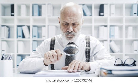 Senior corporate businessman reading paperwork using a magnifier, he is checking carefully an agreement