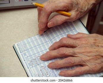 Senior counting money in the checkbook