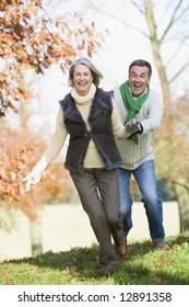 Senior coupl running through autumn woods