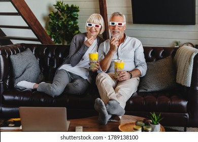 Senior couple with 3D glasses and popcorn sitting on sofa and watching movie at home living room