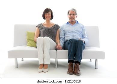 Senior couple affectionately sitting on a white sofa