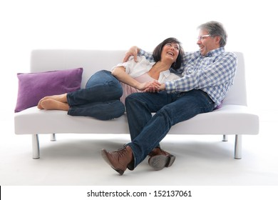 Senior couple affectionately sitting on a white sofa
