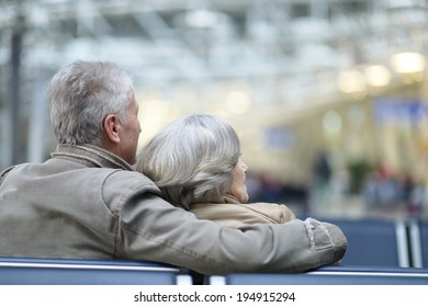 Senior couple at airport sitting on bench